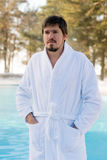 Hombre joven en albornoz cerca de la piscina al aire libre en el invierno Imagen de archivo