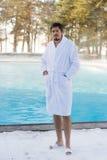 Hombre joven en albornoz cerca de la piscina al aire libre en el invierno Foto de archivo