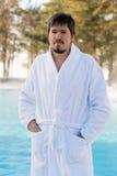 Hombre joven en albornoz cerca de la piscina al aire libre en el invierno Fotos de archivo libres de regalías