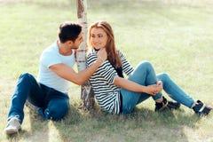 Hombre joven en amor que liga con una muchacha hermosa en fecha al aire libre imagen de archivo libre de regalías