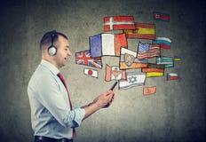 Hombre joven en auriculares que aprende otros idiomas fotografía de archivo libre de regalías