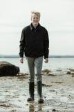 Hombre joven en botas y chaqueta que caminan en la playa Imagen de archivo libre de regalías