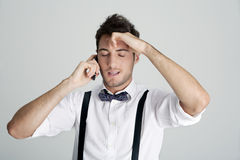 Hombre joven en bowtie en el teléfono y el frus Imagen de archivo
