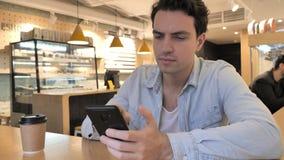 hombre joven en café que hace compras en línea en Smartphone, pago almacen de video