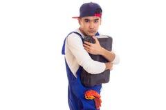 Hombre joven en caja de herramientas que se sostiene total Foto de archivo