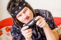 Hombre joven en camisa oscura con los dreadlocks que juegan a los videojuegos con una palanca de mando que se sienta en un sofá a Fotografía de archivo libre de regalías