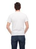 Hombre joven en camiseta blanca en blanco de la parte posterior Foto de archivo libre de regalías