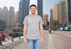 Hombre joven en camiseta gris y vaqueros sobre ciudad Imagenes de archivo