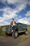 Hombre joven en campo con SUV Imágenes de archivo libres de regalías