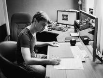 Hombre joven en casa usando un ordenador Imagenes de archivo