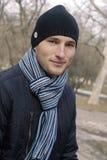 Hombre joven en casquillo negro y bufanda rayada Imagenes de archivo