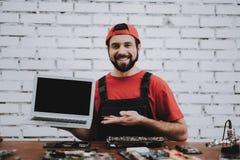 Hombre joven en casquillo rojo con el ordenador portátil fijo en taller fotografía de archivo libre de regalías