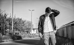 Hombre joven en chaqueta de cuero negra que camina adelante Imagen de archivo libre de regalías