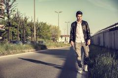 Hombre joven en chaqueta de cuero negra que camina adelante Imagen de archivo