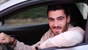 Hombre joven en coche que sonríe a la cámara almacen de video