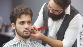 Hombre joven en concepto del servicio del cuidado del cabello de la barbería almacen de metraje de vídeo