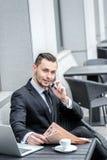 Hombre joven en desgaste formal que habla en el teléfono Foto de archivo libre de regalías