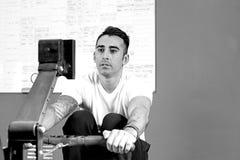 Hombre joven en el aparato de remar - entrenamiento del crossfit Fotografía de archivo libre de regalías