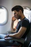 Hombre joven en el avión que habla en el teléfono celular foto de archivo