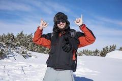 Hombre joven en el bosque del invierno, gozando de la nieve del invierno Imagenes de archivo