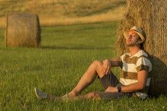 Hombre joven en el campo de trigo que se inclina en pajar Fotos de archivo