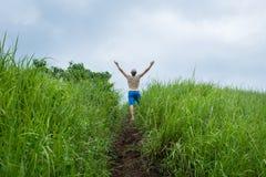 Hombre joven en el campo que sube encima de las manos Fotografía de archivo