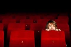 Hombre joven en el cine que oculta detrás de una silla Imágenes de archivo libres de regalías