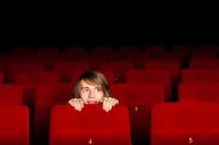 Hombre joven en el cine que oculta detrás de una silla Fotos de archivo libres de regalías