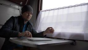 Hombre joven en el comienzo de un tren que trabaja en el ordenador portátil imagen de archivo