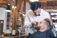 Hombre joven en el concepto de Barber Shop Hair Care Service Imagen de archivo libre de regalías
