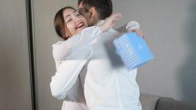Hombre joven en el donante de la caja de regalo de la tarjeta del día de San Valentín a su novia