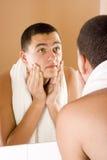 Hombre joven en el espejo del cuarto de baño después de afeitar Fotografía de archivo