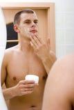 Hombre joven en el espejo del cuarto de baño después del afeitado Foto de archivo libre de regalías