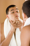 Hombre joven en el espejo del cuarto de baño que limpia su piel Imagenes de archivo