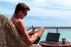 Hombre joven en el funcionamiento del traje de ba?o en un ordenador port?til en un destino tropical Tomar notas sobre un cuaderno fotos de archivo