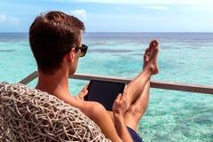 Hombre joven en el funcionamiento del traje de ba?o en una tableta en un destino tropical imágenes de archivo libres de regalías