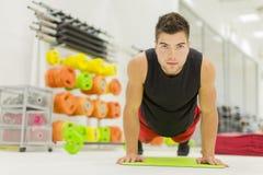 Hombre joven en el gimnasio Foto de archivo libre de regalías