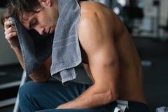 Hombre joven en el gimnasio después de un entrenamiento sólido usando su toalla Foto de archivo libre de regalías