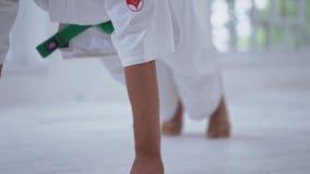 Hombre joven en el kimono blanco que hace ejercicios almacen de metraje de vídeo