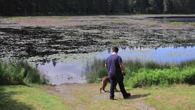 Hombre joven en el lago con el perro almacen de metraje de vídeo