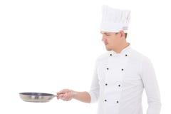 Hombre joven en el sartén que se sostiene uniforme del cocinero aislado en blanco Foto de archivo libre de regalías