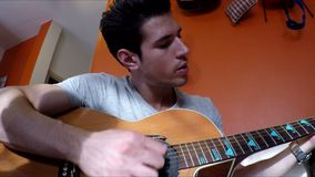 Hombre joven en el sofá que toca la guitarra en casa