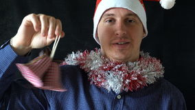 Hombre joven en el sombrero de la Navidad que sostiene campanas del Año Nuevo de una mano del ` s almacen de metraje de vídeo