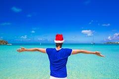 Hombre joven en el sombrero rojo de santa en la playa tropical Foto de archivo