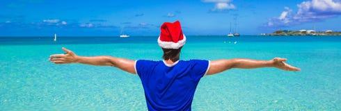 Hombre joven en el sombrero rojo de santa en la playa tropical Imagenes de archivo