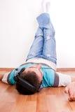 Hombre joven en el suelo con los auriculares Fotografía de archivo