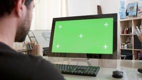 Hombre joven en el taller de los pintores que mira una pantalla verde metrajes