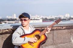Hombre joven en el tejado con una guitarra Foto de archivo libre de regalías