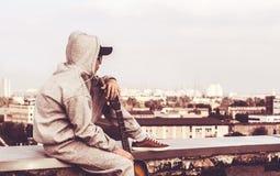 Hombre joven en el tejado con una guitarra Fotografía de archivo libre de regalías