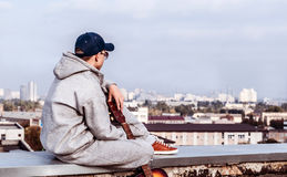 Hombre joven en el tejado con una guitarra Imagen de archivo